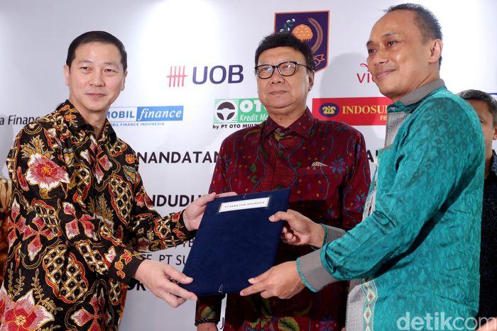 Presiden Direktur PT Bank UOB Indonesia, Kevin Lam, menyerahkan naskah kerjasama kepada Dirjen Dukcapil Kemendagri, Zudan Arif Fakhrulloh, disaksikan Menteri Dalam Negeri (Mendagri) Republik Indonesia, Tjahjo Kumolo, usai penandatangan kerjasama, di Jakarta, Senin (7/8/2017).