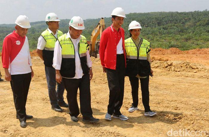 Jokowi meninjau proyek tol Pekanbaru-Kandis-Dumai, Minggu (23/7/2018). Jokowi blusukan dengan mengenakan jaket berlogo The Flash.