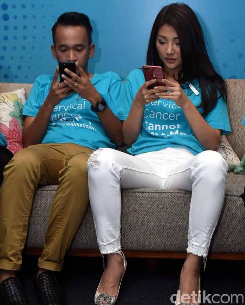 Nah ini nih, ketika keduanya asyik bermain ponsel merek masing-masing, gaya duduk mereka lucu. Sarwendah tampak lebih laki dari sang suami. Foto: Noel