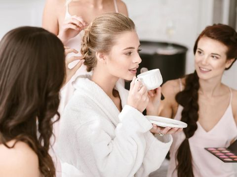 I will be engaged soon. Thoughtful delighted young bride sitting in the white colored room while getting ready with the bridesmaids and drinking tea