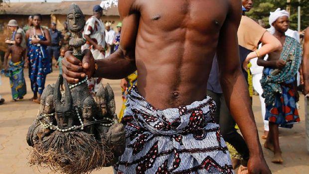 Pemuja membawa boneka voodoo ke kuil (Akintunde Akinleye/Reuters)