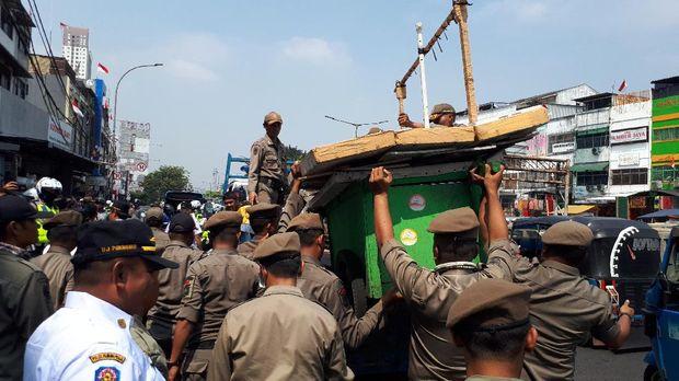 Gerobak PKL yang jualan di trotoar diangkut petugas. Foto: Cici Marlina Rahayu/detikcom
