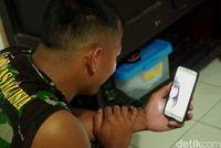 Anggota TNI sedang menghubungi keluarganya