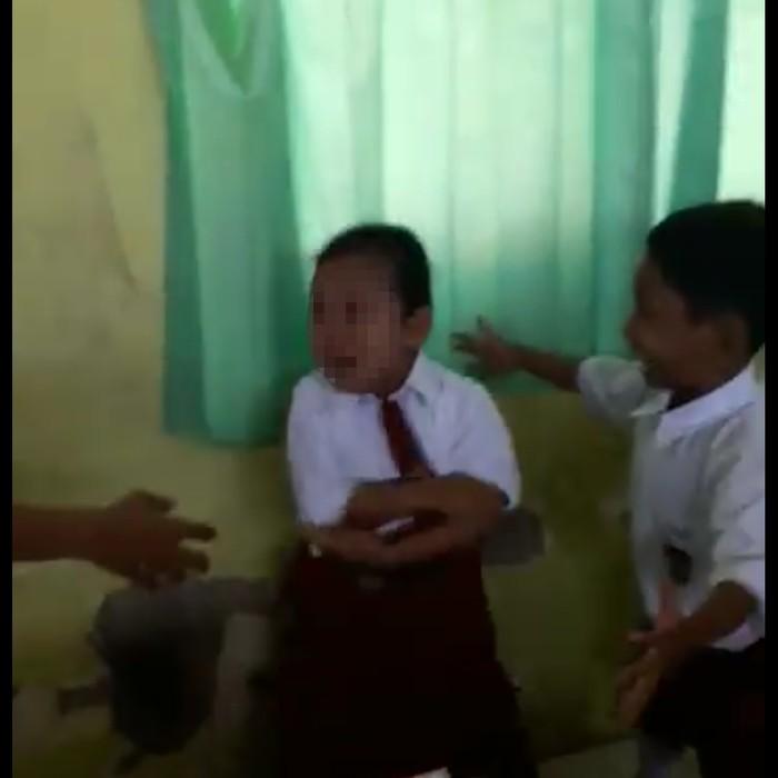 Sang anak berlari-lari di dalam kelas sambil menangis sampai akhirnya terpojok oleh temannya dan seorang guru pria. (Foto: Facebook/Atika Durrotin)