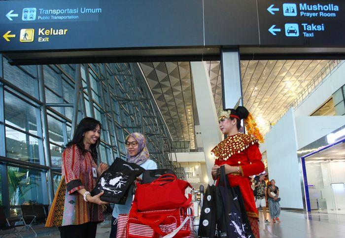 Direktur Airport Service PT. Angkasa Pura II Ituk Herarindri (kedua kiri) memberikan cinderamata kepada penumpang pesawat saat merayakan Hari Pelanggan Nasional 2017 di Bandara Soekarno Hatta, Tangerang, Banten, Senin (4/9). Foto: dok. AP2
