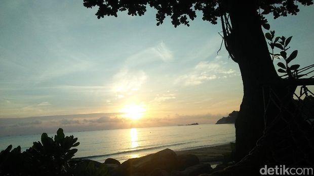 Menikmati sunrise dari hammock di pinggir pantai