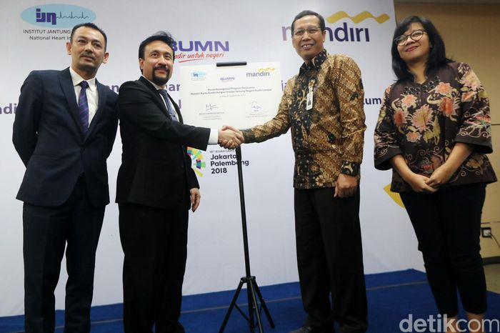 Chief Operating Officer Institut Jantung Negara (IJN) Kuala Lumpur Akmal Arief Mohamed Fauzi berjabat tangan dengan Direktur Retail Banking Bank Mandiri Tardi usai penandatanganan kerja sama di Jakarta, Rabu (6/9/2017).