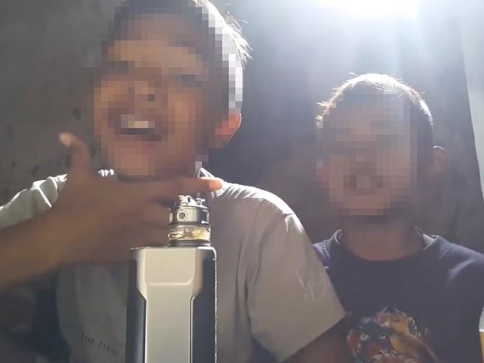 Layaknya video blogger (vlogger) kawakan, dua bocah ini mengenalkan diri dan menunjukkan bahwa mereka kedapatan produk cairan rokok elektrik yang terbaru. (Foto: Facebook/Meme Politik Indonesia)