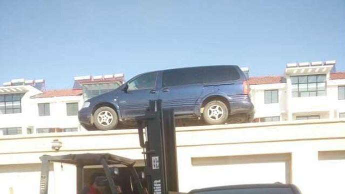 Rasakan! Parkir Sembarangan Mobil Ini Dipindahkan ke Atap Rumah