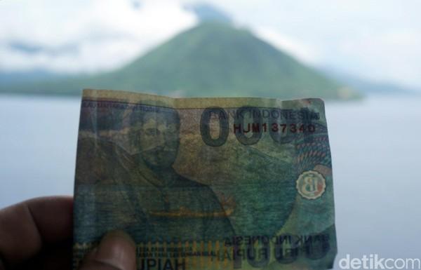 Kalau bawa uang seribu rupiah lama, boleh dikeluarkan lho traveler. Kamu bisa berfoto dengan Pulau Maitara untuk dicocokkan gambarnya dengan uang asli (Wahyu/detikTravel)