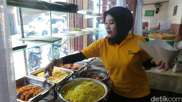 Pelayan Rumah Makan Al Hikmah akan dengan sigap melayani nasi kuning pesanan traveler. Seporsi nasi kuning dihargai sekitar Rp 16 ribu saja (Wahyu/detikTravel)