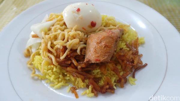 Seporsi nasi kuning berisi nasi kuning, dengan topping kering kentang pedas, mie, ikan tongkol, serta telur rebus. Sebagai pelengkapnya ada acar dan juga sambal pedas (Wahyu/detikTravel)