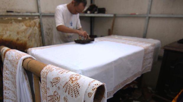 Seorang perajin mencetak kain batik khas Betawi menggunakan malam atau lilin yang dipanaskan di kawasan Terogong, Cilandak, Jakarta.