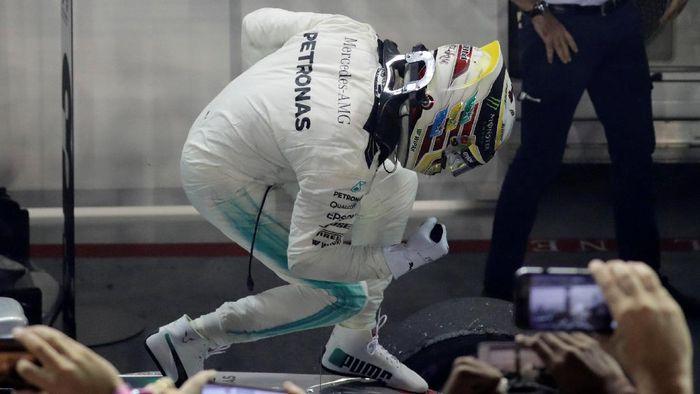 Lewis Hamilton merayakan kemenangannya di Singapura (Jeremy Lee/Reuters)