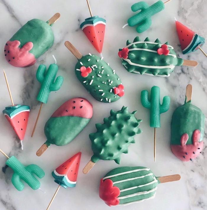 Berbekal kemampuan otodidak, Raymond Tan membuat aneka cake popsicles cantik. Cake dilapisi cokelat cair lalu dihiasi fondant. Yang ini bertema kaktus dengan warna hijau dan merah menggemaskan.