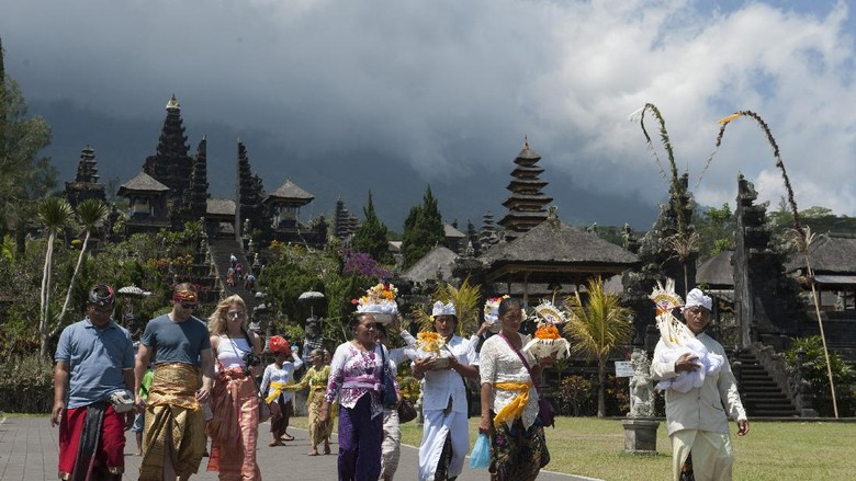 Sejumlah wisatawan beraktifitas di Pura Besakih yaitu Pura yang berada di kaki Gunung Agung, Karangasem, Bali, Selasa (19/9). Pusat Vulkanologi dan Mitigasi Bencana merekomendasikan zona larangan aktifitas hingga enam kilometer dari puncak Gunung Agung menyusul meningkatnya aktifitas gunung tertinggi di Bali itu hingga pada level siaga. ANTARA FOTO/Nyoman Budhiana/pd/17.