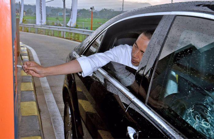 Dari kursi penumpang, Jokowi menjulurkan tangannya untuk menempelkan e-Toll ke mesin transaksi. Mobil pun melaju di tol yang diklaim terindah itu. (Agus Suparto/Setpres).