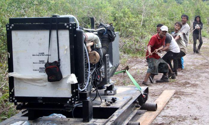 Petugas PLN menarik mesin melewati hutan di Pulau Pongok dan Celagen, Kabupaten Bangka. (PLN).