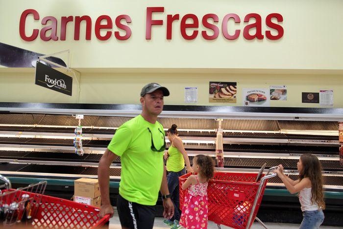 Warga lokal di tengah rak makanan yang kosong di San Juan, Puerto Rico, (30/9) pasca Badai Maria lebih dari satu pekan lalu. Pemerintah setempat menyatakan perlu waktu satu bulan untuk memulihkan perekonomian.