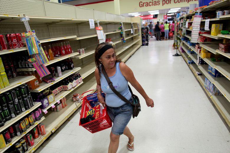 Warga mencari sisa makanan di supermarket yang sudah hancur akibat Badai Maria di San Juan, Puerto Rico, (30/9). Kota yang terkenal dengan lagu Luis Fonsi Despacito tersebut hancur oleh kecepatan angin badai hingga 250km per jam.