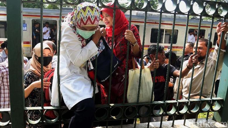 Foto: Dampak Anjlok, Penumpang KRL Nekat Naik Pagar Tinggi