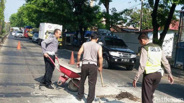 Polisi tambal jalan berlubang di Pantura, Pekalongan.