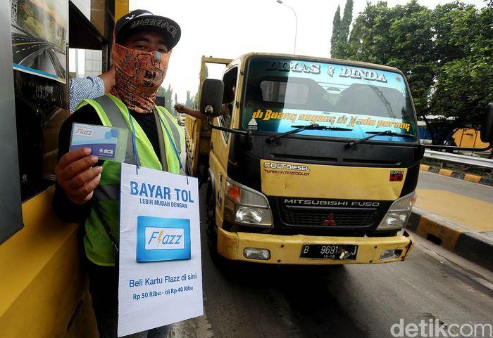 Petugas dari PT Jalan Tol Lingkar Luar Jakarta (JLJ) selaku operator ruas tol Jakarta Outer Ring Road (JORR), mensosialisasikan penggunaan kartu tol elektronik kepada para pengendara di ruas Tol JORR Jati Asih, Kota Bekasi.