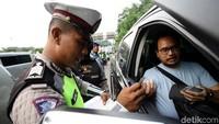 Polisi memeriksa surat-surat kendaraan yang terjaring razia.