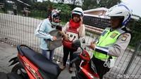 Polisi memeriksa kelengkapan surat-surat pengendara sepeda motor.