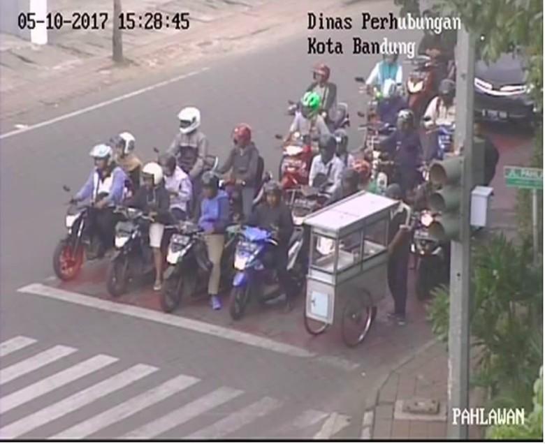 Pedagang kaki lima (PKL) ini menuai pujian dari warganet. Dia yang mendorong gerobak saja mematuhi peraturan lalu lintas untuk berhenti sebelum garis stop di lampu merah. Foto: Pool (Instagram)
