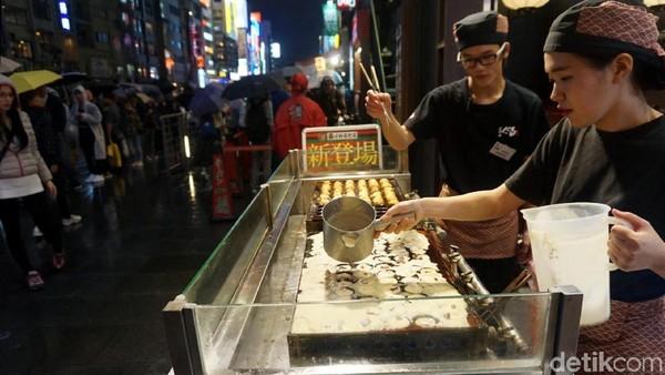 Di bagian depan kedai, traveler bisa melihat aksi pelayan memasak ketika memasak takoyaki. Satu orang menuang adonan, sedangkan yang satu lagi membolak-baliknya (Wahyu/detikTravel)