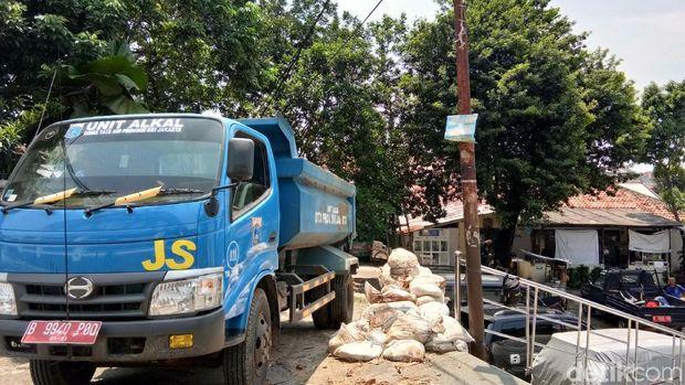 Petugas memperbaiki tanggul karung jebol di Kali Pulo, Jatipadang, Jakarta Selatan