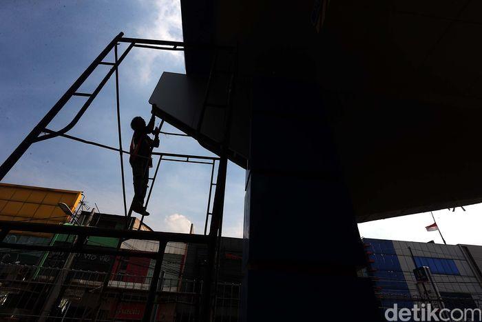 Pekerja mengerjakan penyelesaian akhir pembangunan gerbang tol Becakayu, Sabtu (21/10/2017).