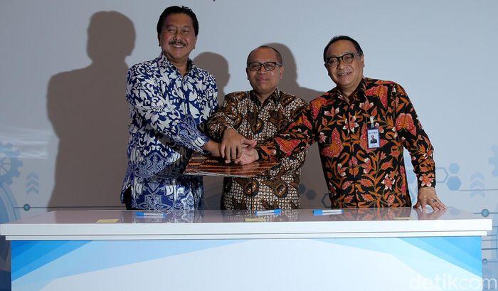 Dirut Peruri Prasetio (kiri), Dirut BPJS Agus Susanto (tengah) dan Dirut BTN Maryono saling bertumpu tangan usai menandatangani nota kesepahaman tentang pemberian fasilitas kredit kepemilikan rumah, di Jakarta, Selasa (24/10/2017).