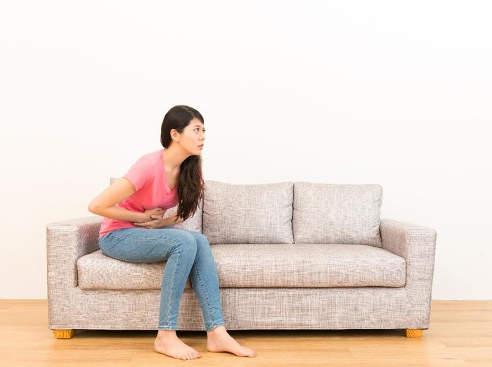 young woman sitting on sofa making pain gesture