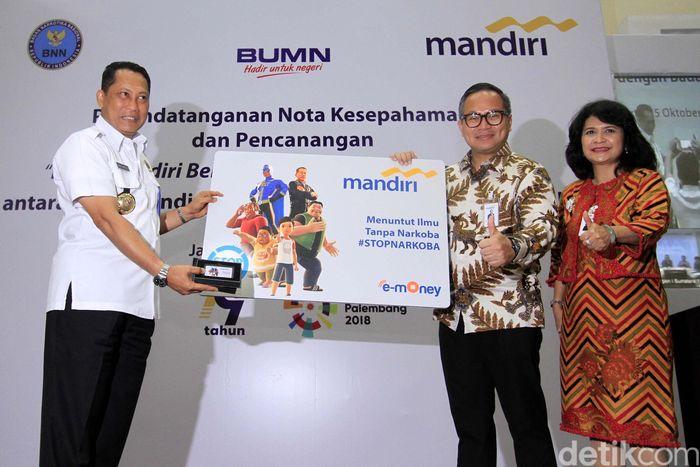 Kepala BNN Komjen Pol. Budi Waseso (kiri), Dirut Bank Mandiri Kartika Wirjoatmodjo (tengah) dan Direktur Kelembagaan Bank Mandiri Kartini Sally (kanan) menunjukkan contoh kartu e-money edisi khusus Kampanye Anti Narkoba di Plaza Mandiri, Jakarta, Rabu (25/10).