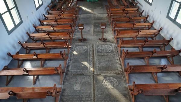 Terdapat 30 batu nisan yang disusun menyerupai salib di dalam ruangan gereja. Kita dapat melihat dan membaca dengan jelas nama-nama serta identitas prajurit yang dimakamkan di situ (Syanti/detikTravel)