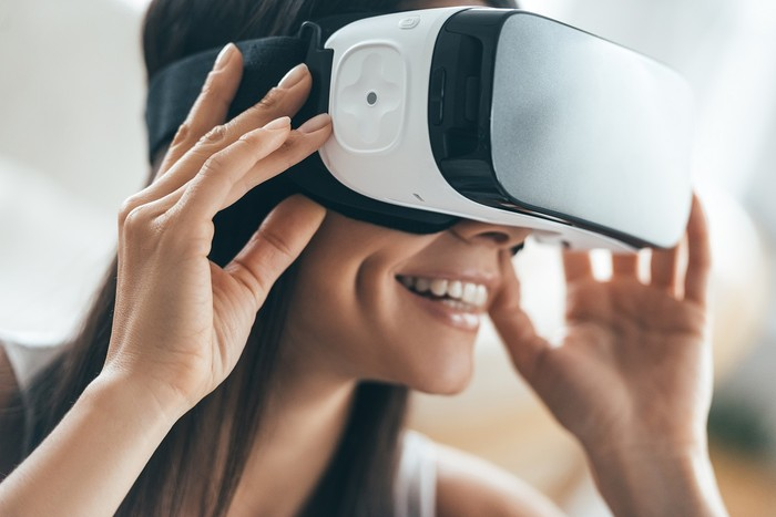 Attractive young woman adjusting her VR headset and smiling while sitting at home
