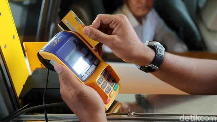 Petugas melayani pengendara untuk melakukan pengisian e-money di Pintu Tol Meruya Utara 3, Jakarta, Jumat (27/10/2017). Pengendara hanya cukup lapor kepada petugas untuk melakukan pengisian e-money, lalu petugas akan membantu untuk melakukan pengisian. Grandyos Zafna/detikcom
