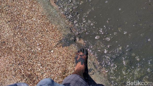 Pantai berlumpur hitam dan berbau tak sedap.