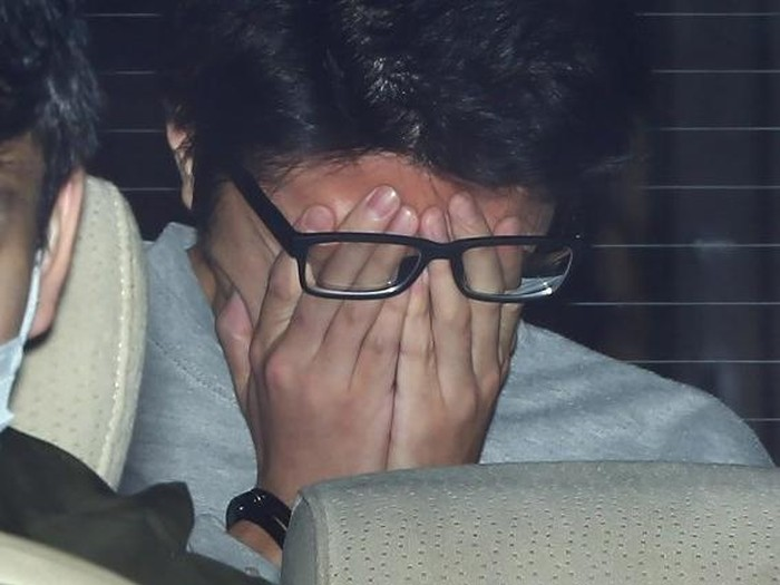 Suspect Takahiro Shiraishi covers his face with his hands as he is transported to the prosecutors office from a police station in Tokyo on November 1, 2017.  The 27-year-old Japanese man, who was arrested after police found nine dismembered corpses rotting in his house, has confessed to killing all his victims over a two-month spree after contacting them via Twitter, media reports. / AFP PHOTO / JIJI PRESS / STR / Japan OUT