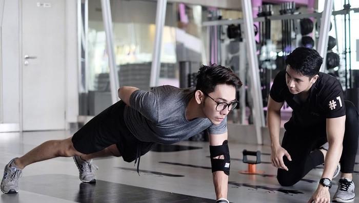Presenter John Martin lakukan latihan pembentukan otot bersama pelatih kebugaran pribadi. Foto: Instagram @itsjohnmatint
