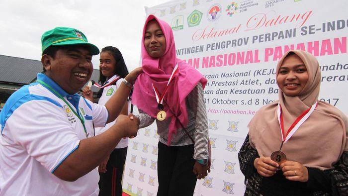 Wakil Ketua Panitia Pertandingan, Anwar Thaib (kiri) menyerahkan medali emas secara simbolis kepada pepanah putri Jawa Timur Bunga Arbela (kedua kanan) di Kejurnas Panahan 2017. (Ampelsa/Antara)
