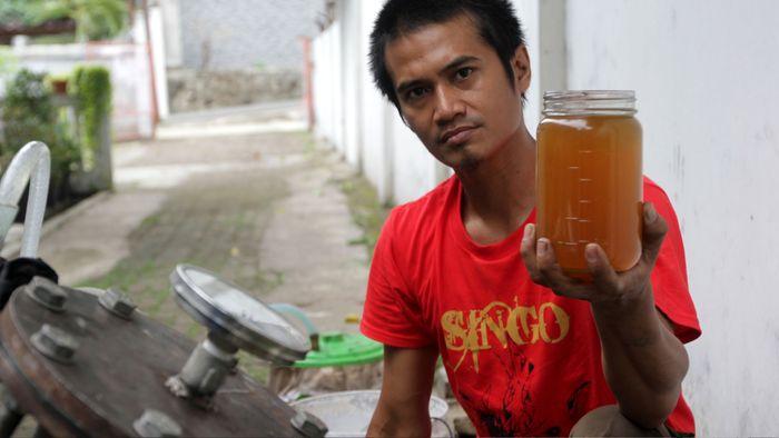 Dimas menunjukkan bahan bakar minyak yang terbuat dari limbah plastik di kawasan Pengadegan, Pancoran, Jakarta.