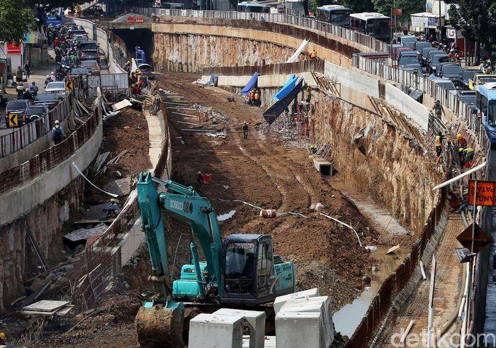 Pekerja menyelesaikan pembangunan underpass Mampang-Kuningan, Jakarta.