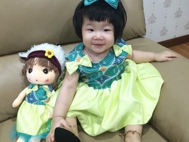 Pakai kostum samaan bernuansa hijau gini, bikin si kecil sama bonekanya makin kompak. (Foto: Instagram/ @litawatylim)