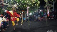 Salah seorang penari mengelilingi bambu berbalut kain merah (Syanti/detikTravel)