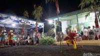 Penari mengelilingi 5 bambu yang tertancap di halaman Rumah Adat (Syanti/detikTravel)