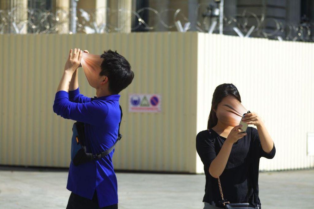 Fotografer asal Perancis Antoine Geiger menjepret orang memakai ponselnya di publik, kemudian memodifikasinya sehingga seakan ponsel itu merekat ke wajah mereka. Foto: istimewa