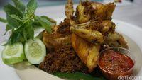 Ayam goreng bumbu kuning yang disajikan dengan lalapan dan sambal dari Redjeki Kuliner.